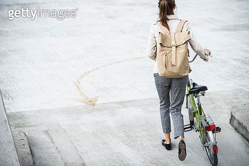 Young businesswoman with backpack, pushing bicycle, rear view - gettyimageskorea