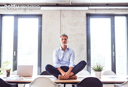 Mature businessman sitting barefoot on desk in office meditating - gettyimageskorea
