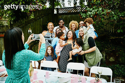 Woman taking photo with smartphone of smiling multi-generation family at backyard birthday party - gettyimageskorea