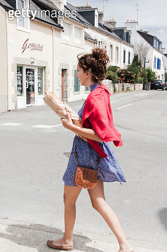 Woman walking in the street with a french baguette under her arm - gettyimageskorea