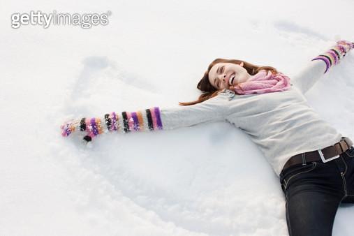 Woman making snow angel - gettyimageskorea