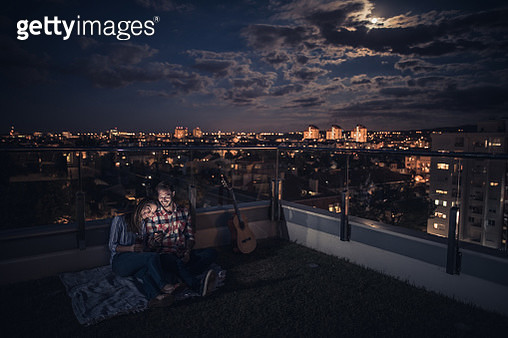 Young smiling couple relaxing on a penthouse terrace by night and using cell phone. - gettyimageskorea