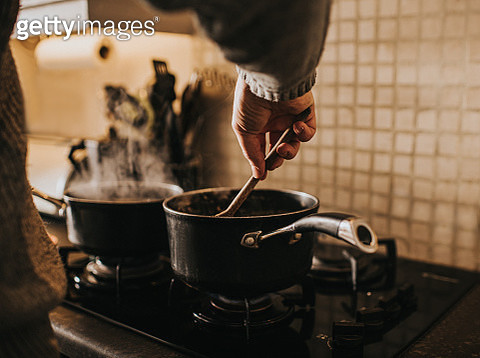 A male cooking on a gas hob in the evening time. Stirring with a wooden spoon. - gettyimageskorea
