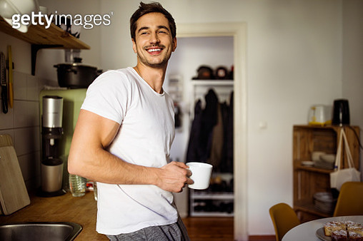 Handsome young man standing in kitchen with a cup of coffee at home - gettyimageskorea