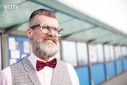 Portrait of stylish senior man with eyeglasses and handlebar moustache on pier - gettyimageskorea
