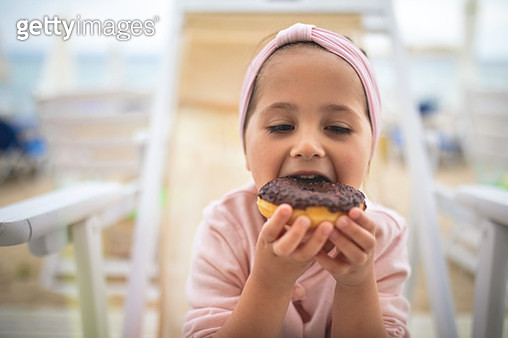 Little girl eating a donut - gettyimageskorea