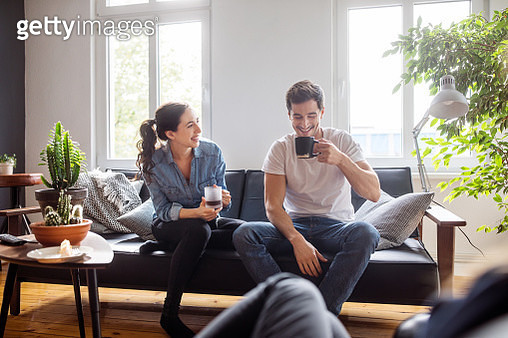 Cheerful young man and woman sitting on sofa in living room having coffee and talking - gettyimageskorea