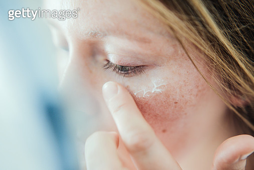 Woman applying skin face cream. - gettyimageskorea