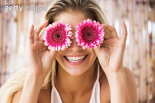 Young blonde woman holding flowers to cover her eyes, smiling - gettyimageskorea