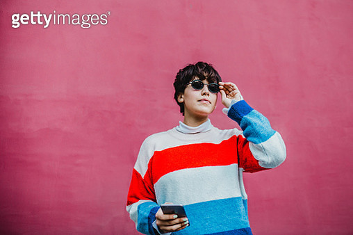 Photo of a young woman with sunglasses standing on the street and holding smartphone - gettyimageskorea