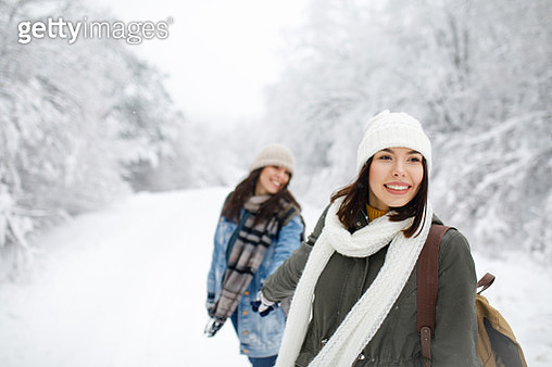 Two smiling women are walking in the park in winter. Friends with backpacks go through the forest. Girls in knitted hats and winter jackets against the background of a snowy forest. - gettyimageskorea
