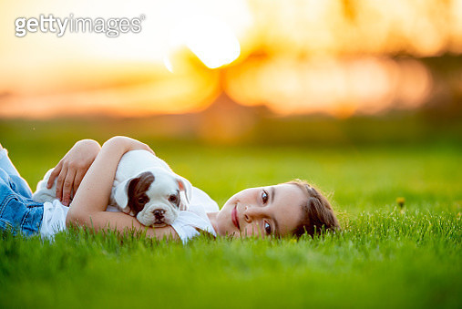 A young girl is outdoors in a green field with a small puppy . She is holding the pup in her hand while laying on the grass. Both the pup and the girl look happy. - gettyimageskorea