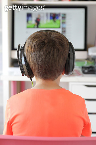 Rear view of boy playing video game - gettyimageskorea