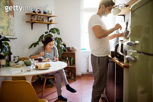 Woman checking her mobile phone and having breakfast  with man preparing coffee in kitchen at home - gettyimageskorea