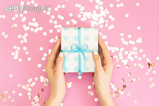 Womans hands holding gift or present box decorated confetti on pink pastel table top view. Flat lay composition for birthday or wedding - gettyimageskorea