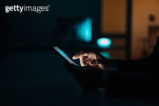 Close-up of businessman working late in office using tablet - gettyimageskorea