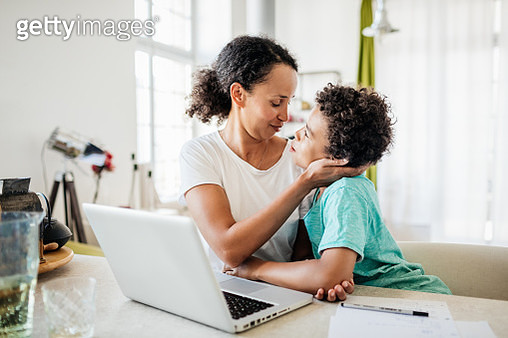 A single mom being affectionate with her young son while working from home on her laptop. - gettyimageskorea