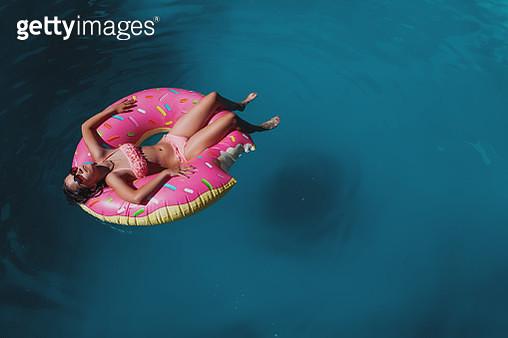 brunette teen in donuts inflatable ring. - gettyimageskorea