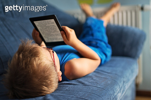 Little boy reading an ebook on couch - gettyimageskorea