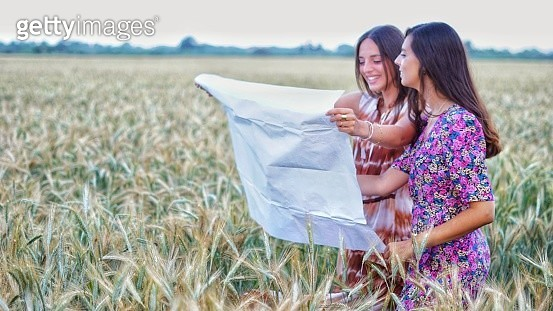 Woman Smiling On Field Looking At A Map - gettyimageskorea