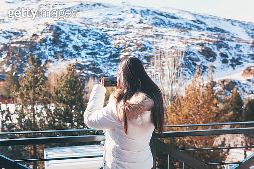young woman in ski clothes taking selfie in snow with smartphone - gettyimageskorea