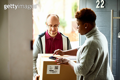 Courier delivering package to customer at front door, technology, efficiency, convenience - gettyimageskorea