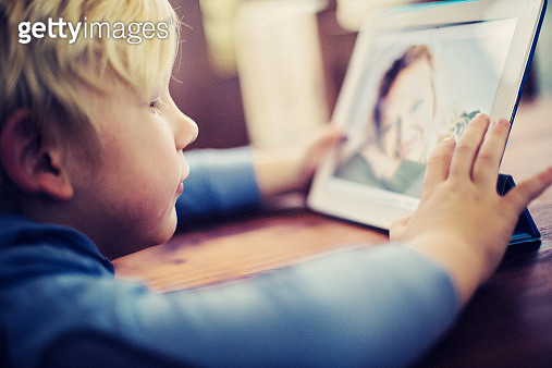 Little boy talking to his Mother on an electronic tablet over the internet - gettyimageskorea
