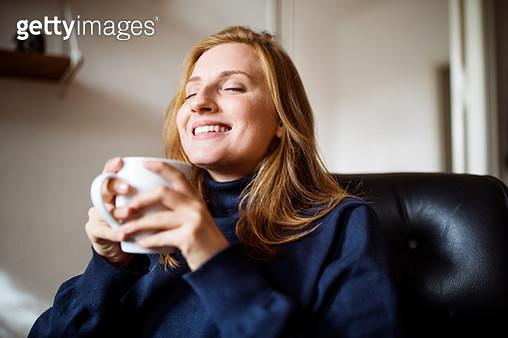 Smiling woman having coffee at home - gettyimageskorea