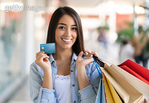 Beautiful young woman enjoying herself at the mall holding her credit card and bags while looking at camera smiling - gettyimageskorea