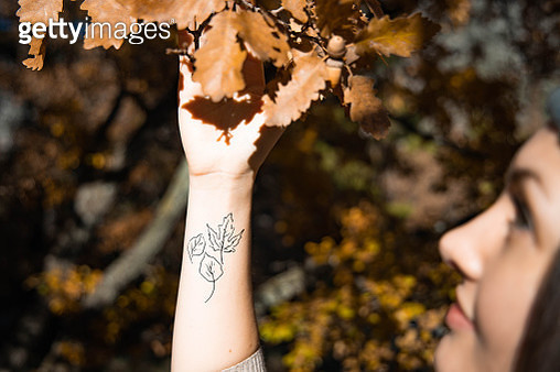 Woman in autumn nature with tattoo leafs on wrist. - gettyimageskorea