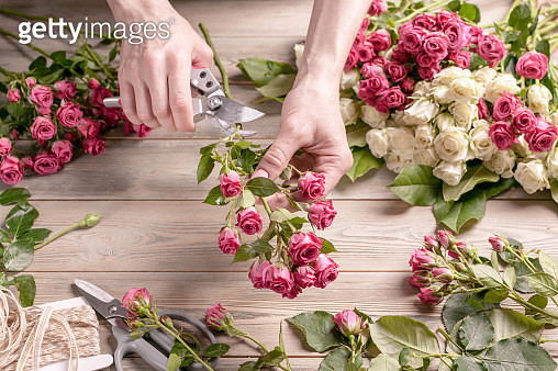 Cropped Hands Of Person Holding Pink Roses On Table - gettyimageskorea