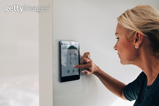 Blond woman adjusting thermostat using digital tablet mounted on white wall at home - gettyimageskorea