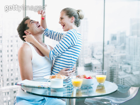 Playful woman feeding strawberry to husband at breakfast - gettyimageskorea