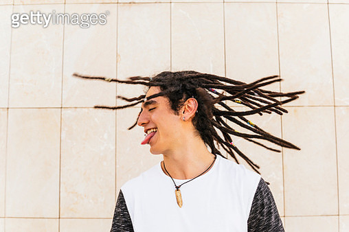 Man with dreadlocks shaking head while sticking out tongue in front of wall - gettyimageskorea