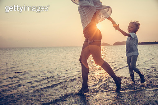 Mother And Son Running Along Beach - gettyimageskorea