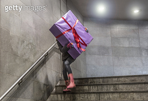 Young girl running with large gift at Christmas - gettyimageskorea