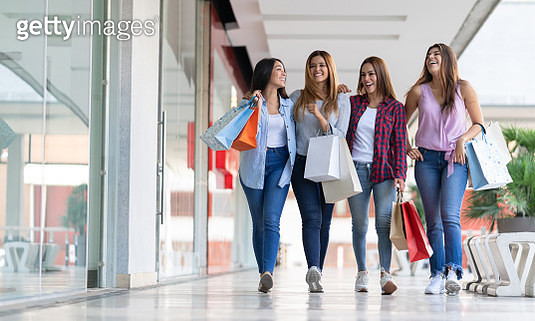 Excited group of friends walking around the mall talking and laughing while holding shopping bags - gettyimageskorea