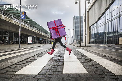 Young girl running with large gift on street - gettyimageskorea