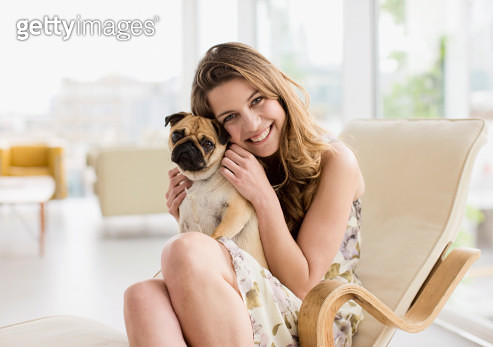 Smiling woman holding cute, small dog on lap - gettyimageskorea