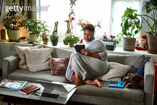 Candid portrait of woman relaxing on sofa with digital tablet - gettyimageskorea