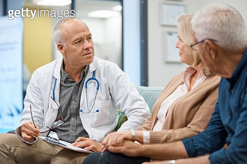 Professional doctor consulting senior couple. Elderly patients are discussing regarding their health with expert. They are sitting in hospital. - gettyimageskorea