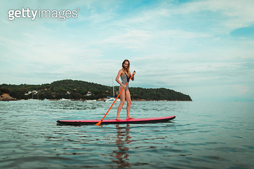 Woman learning how to paddle board at the seaside in Greece on a summer day - gettyimageskorea