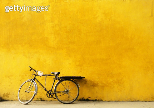 Unattended bicycle leaning on yellow wall in Hoi An, Vietnam. - gettyimageskorea