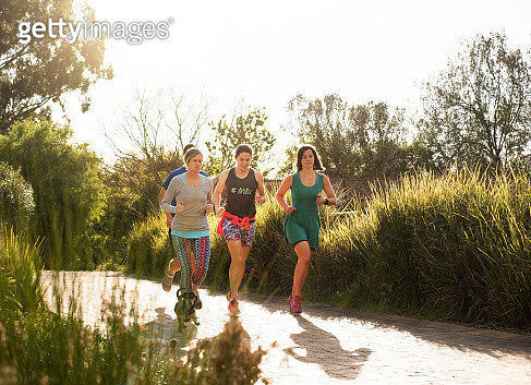 Shot of a man and women running together in a park on a sunny morning - gettyimageskorea