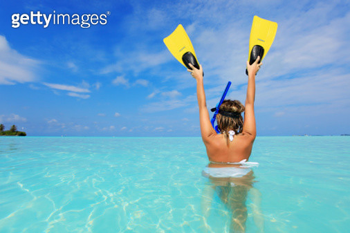 Female diver at the sea holding flippers in raised hands - gettyimageskorea