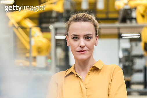 Portrait of confident woman in factory shop floor with industrial robot - gettyimageskorea