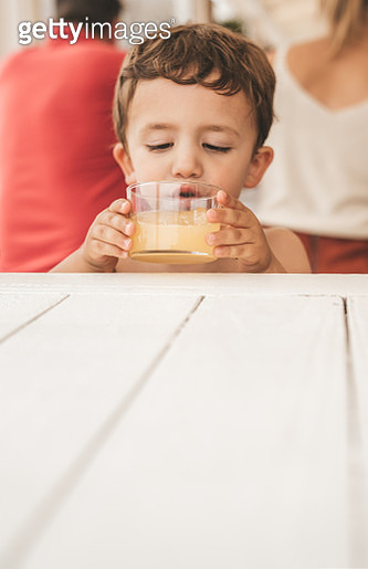 Boy having juice at the beach - gettyimageskorea