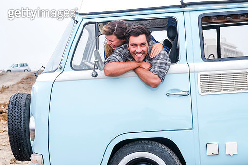 Spain, Tenerife, portrait of laughing man and his girlfriend leaning out of car window of camper - gettyimageskorea