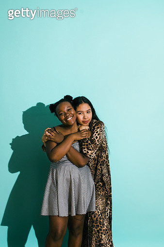 Bisexual couple hugging on a Turquoise background. Couple is looking into the camera. Part of the LGBTQ Portrait series. - gettyimageskorea