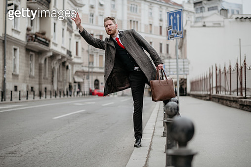 Businessman calling taxi in the street - gettyimageskorea